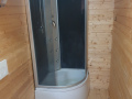 Starý sprchový kout s vysokou vaničkou.
